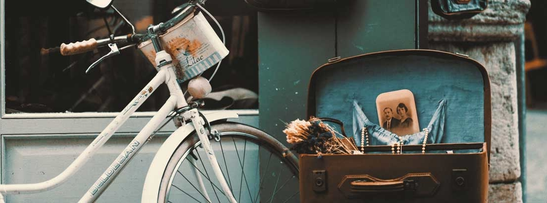Bicicleta blanca antigua junto a maleta vieja abierta sobre una banqueta tapizada.