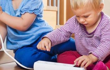 Dos niños pequeños juegan con un enchufe
