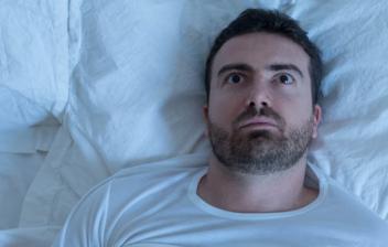 Un hombre tumbado en la cama con los ojos abiertos mirando al techo porque no puede dormir.