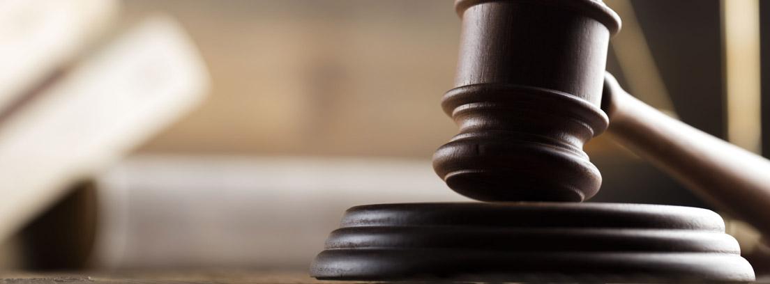 Mesa de madera sobre la que se encuentran el mazo de un juez, una balanza y un libro abierto. Al fondo el juez con su toga.