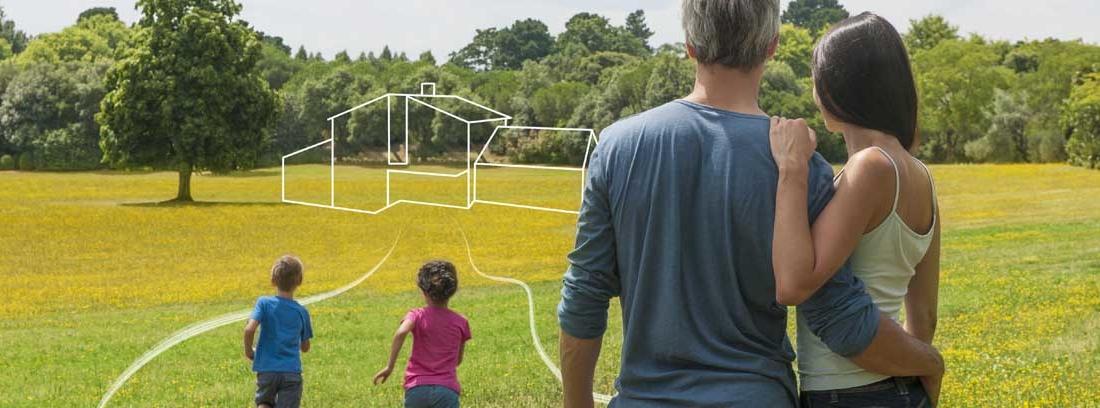 Hombre y mujer de espaldas abrazados observando un terreno con líneas dibujadas que forman una casa, y dos niños corriendo delante de ellos.