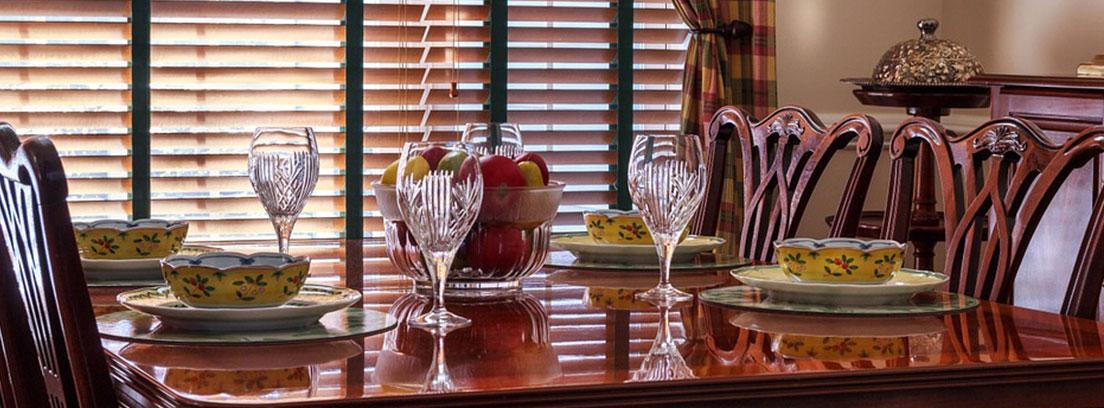 Mesa de comedor con copas y vajilla y ventana con persiana veneciana de madera