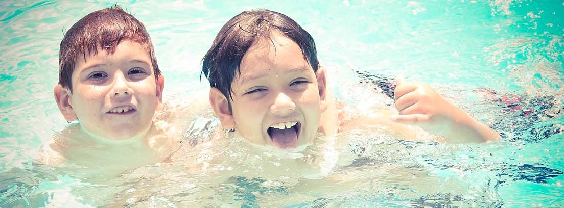 Dos niños dentro del agua con la cabeza y una mano fuera