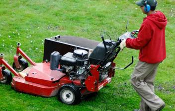 Joven usando una máquina cortacésped para arreglar el jardín