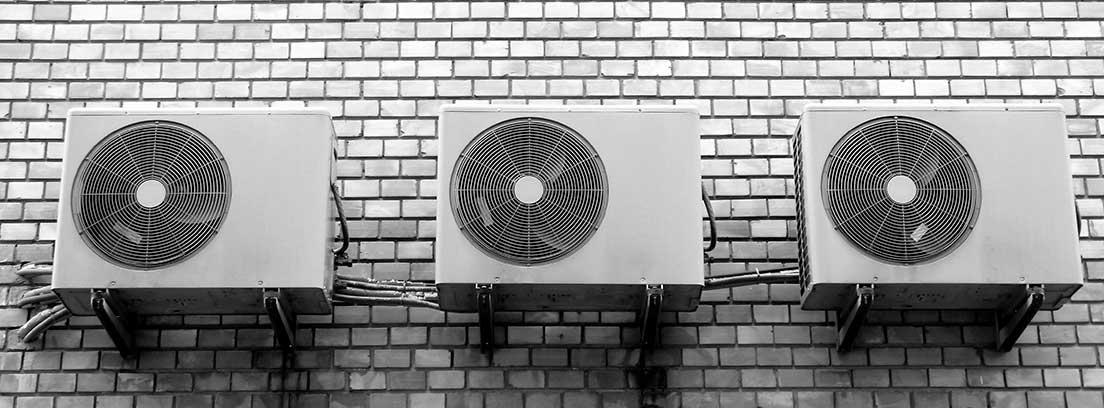 Tres aparatos de aire acondicionado colgados en una pared de ladrillo blanco