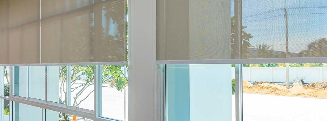 Cortinas tipo screen marrones a media altura sobre dos ventanales que dan a una calle soleada