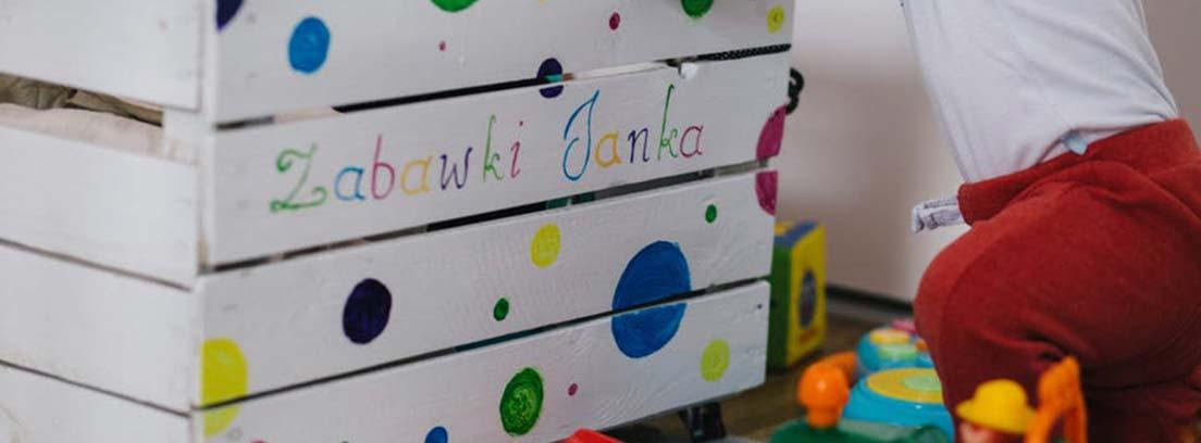 Caja de listones blanca con puntos de colores en el borde se apoya un niño