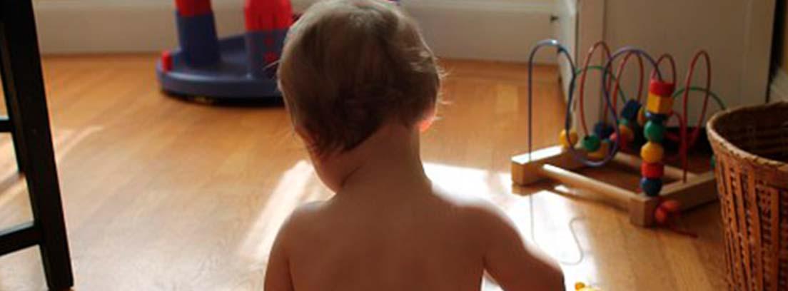 Bebe de espaldas con pañal sentado sobre el suelo de madera junto a un pato de juguete