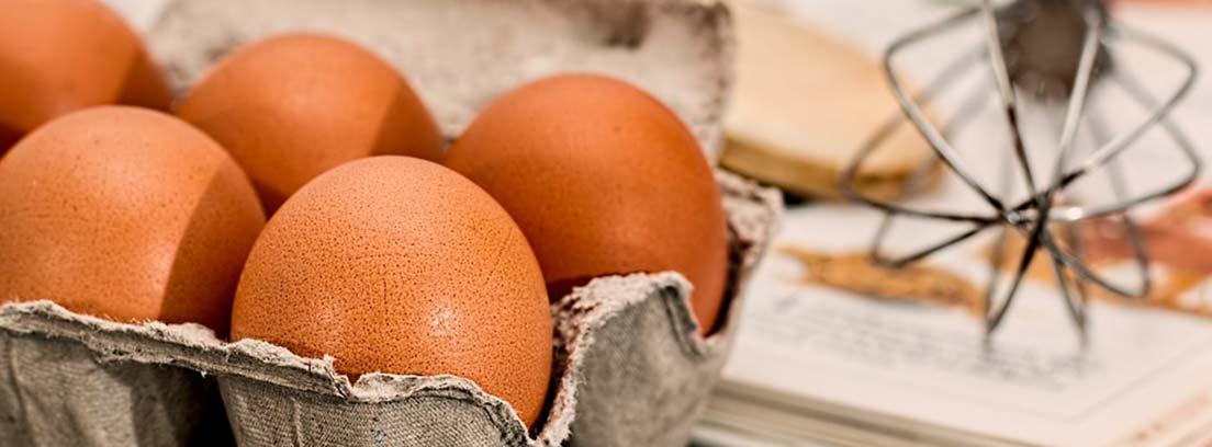 Huevos morenos en una huevera de cartón gris y junto a un batidor manual de hierro