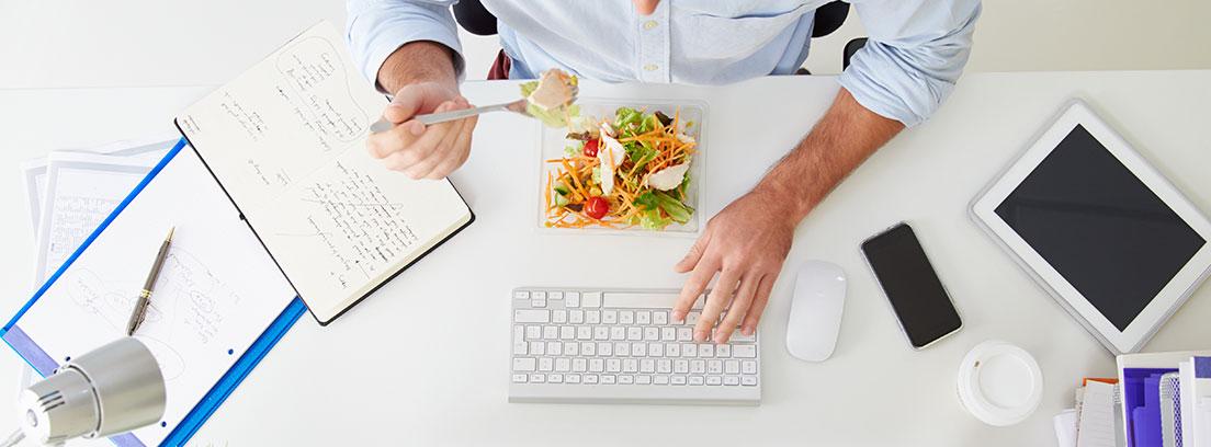 Vista superior de mesa con ordenado, recipiente con ensalada y hombre comiendo