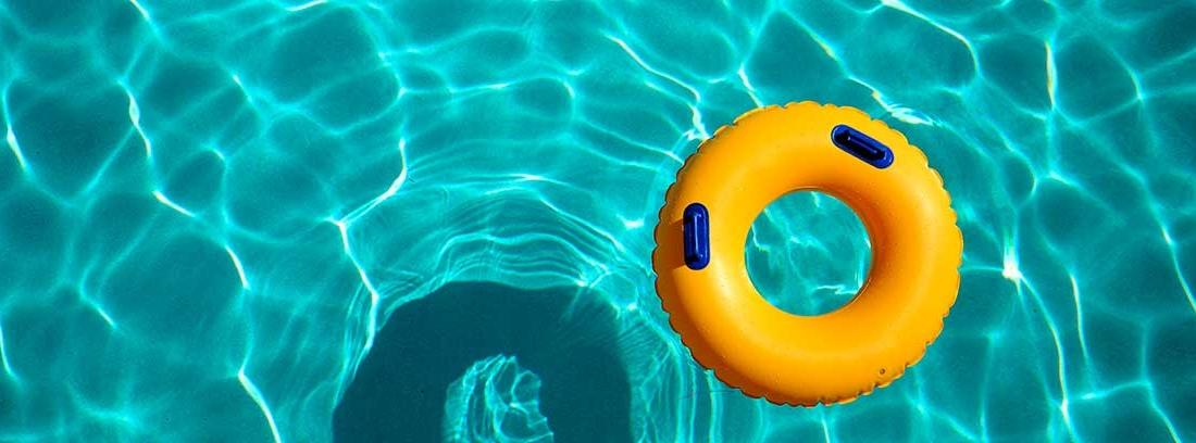 Un flotador amarillo y azul flota sobre el agua de una piscina