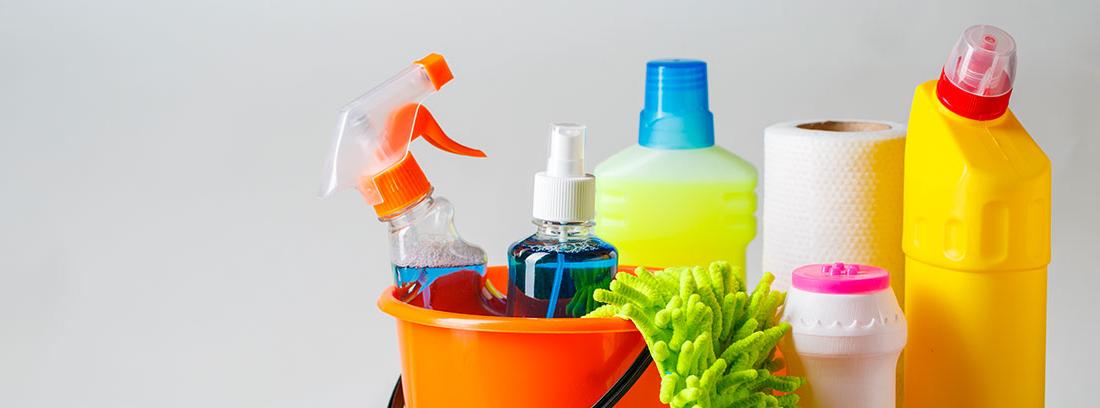 diferentes productos de limpieza con cepillo y mopa junto a un cubo de color naranja