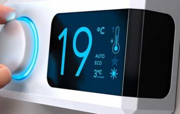 regulador de temperatura digital blanco, una mano acciona una ruleta. En la pantalla se marcan 19 ºC
