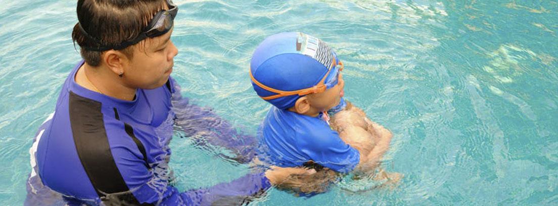 Hombre de pie dentro del agua sujeta a niño con gafas y gorro de natación.