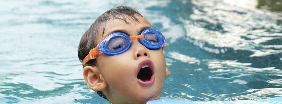 Niño en el agua con gafas de bucear azules y naranjas sobre los ojos y boca abierta.