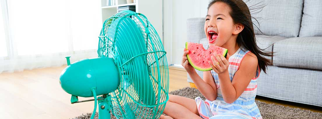 Niña comiendo una rodaja de sandía sentada en una alfombra frente a un ventilador azul