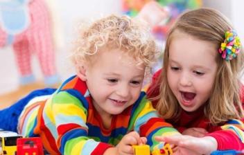 Dos niños tumbados boca abajo en el suelo rodeados de juguetes