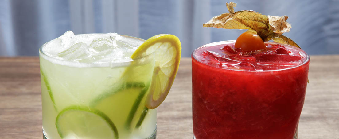 Vaso con contenido verde claro, limas y limones junto a otro con líquido rojo.