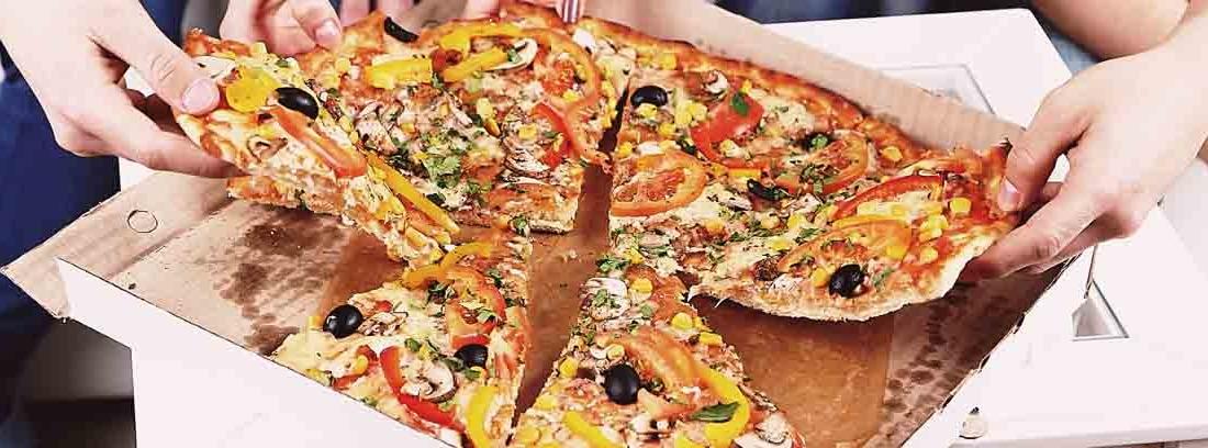 Varias manos cogen un trozo de pizza que se encuentra en una caja