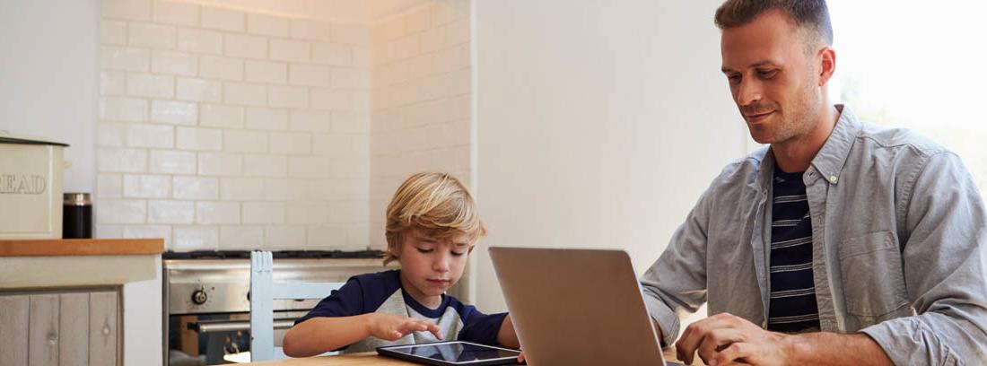 Hombre sentado en mesa de cocina con portátil y niño a su lado con tableta.