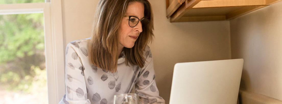Mujer con gafas con manos sobre portátil sobre encimera de cocina y junto a vaso