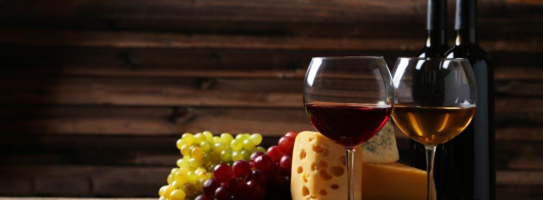 Copas de vino tinto y blanco, quesos y uvas, el maridaje de vinos perfecto