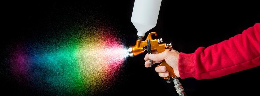 Mano sujetando un aerosol de pintura del que salen varios colores de pintura de coche
