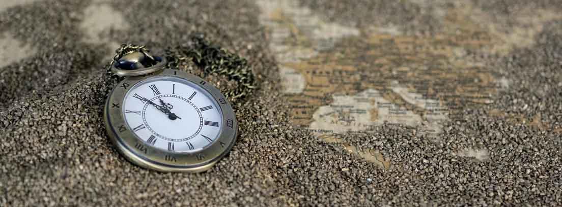 Reloj de mano sobre un mapa de Europa cubierto de arena