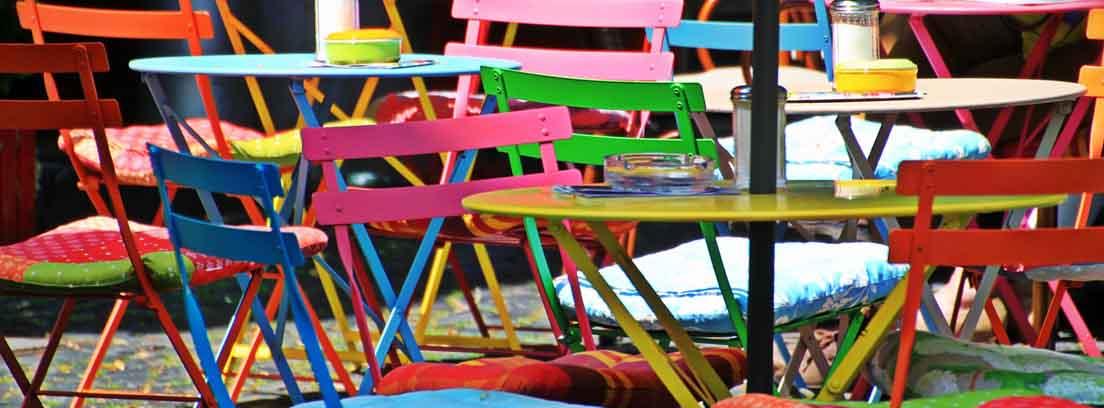 Sillas metálicas de diferentes colores vivos alrededor de mesa