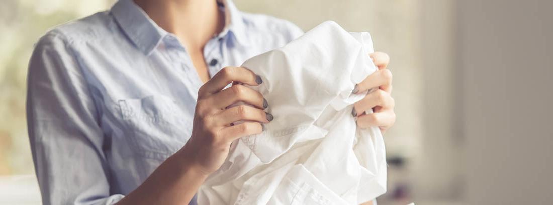 Mujer sostiene ropa entre sus manos sobre cesto lleno de prendas