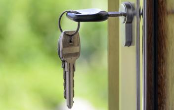 Llave colgando de cerradura de seguridad en una puerta de madera
