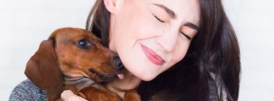 Mujer con su perro marrón en brazos.