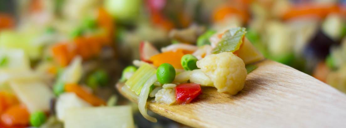 Cuchara de palo con una porción de un plato de ensaladilla rusa