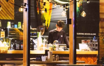 Gran ventanal deja ver persona joven con camisa negra tras de una barra de cafetería.