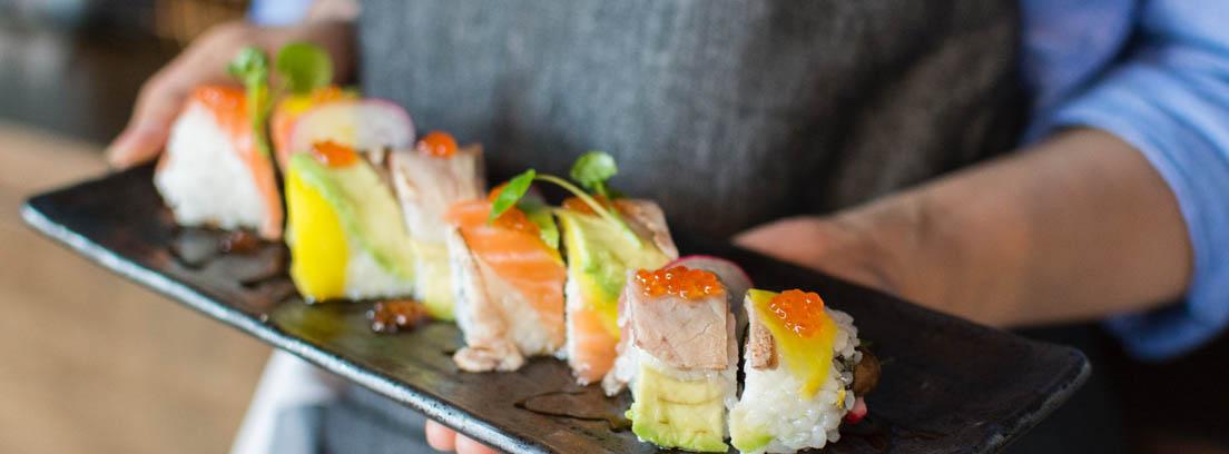 Bandeja rectangular negra con hilera de trozos de comida con salmón y huevas.