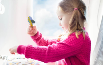 Niña con la edad mínima para viajar solo en avión sentada en el interior de uno