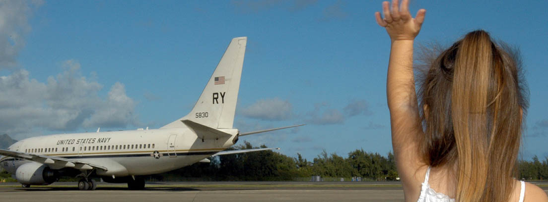 Niña de espaldas con la mano en alto diciendo adiós a un avión a lo lejos