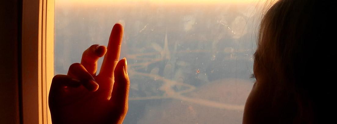 Silueta de una niña asomada por la ventana de un avión