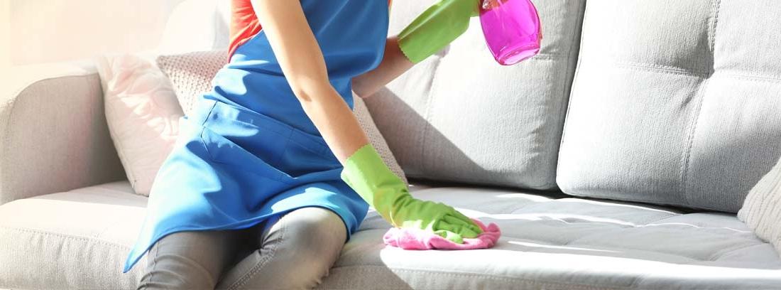 Mujer sonriente con delantal y guantes aplicando un spray y una bayeta sobre un sofá gris