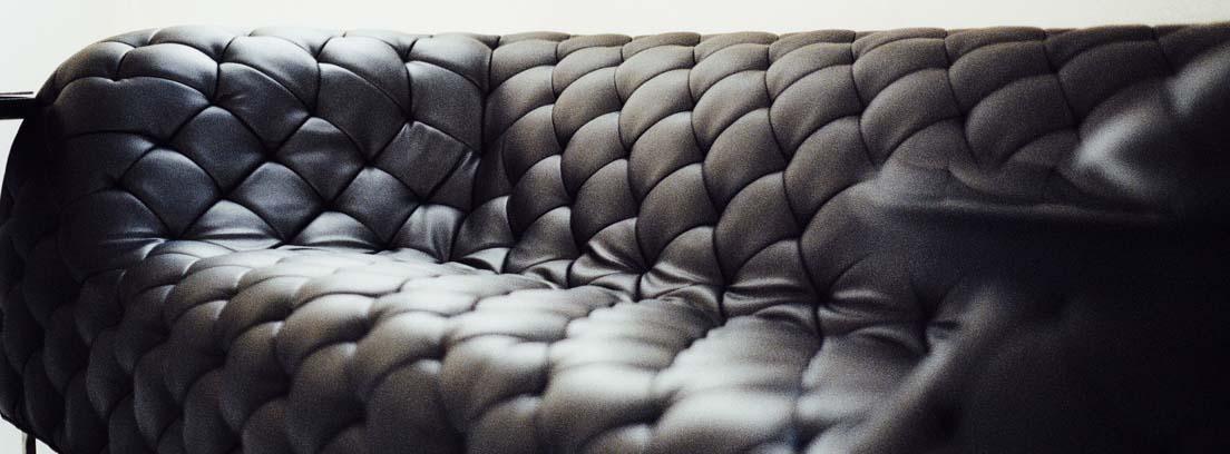 Sofá de cuero negro con capitoné