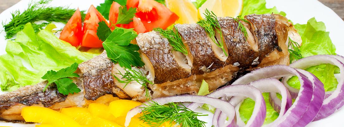 plato de pescadilla con tomate, cebolla y lechuga