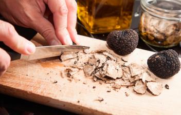 hombre partiendo con cuchillo trufa negra en tabla de madera