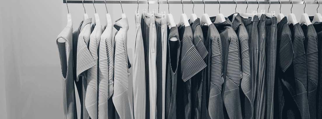 Perchero con varias prendas de ropa de tonos grises