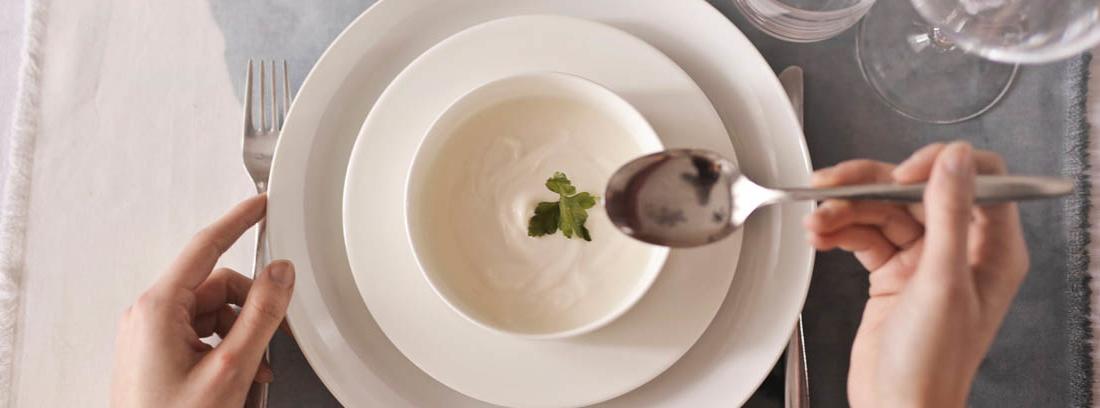 Mano con cuchara sobre cuenco con crema blanca