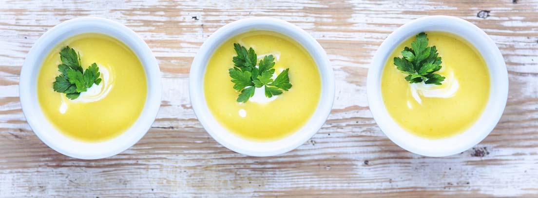 Tres cuencos blancos con crema amarilla y hojas