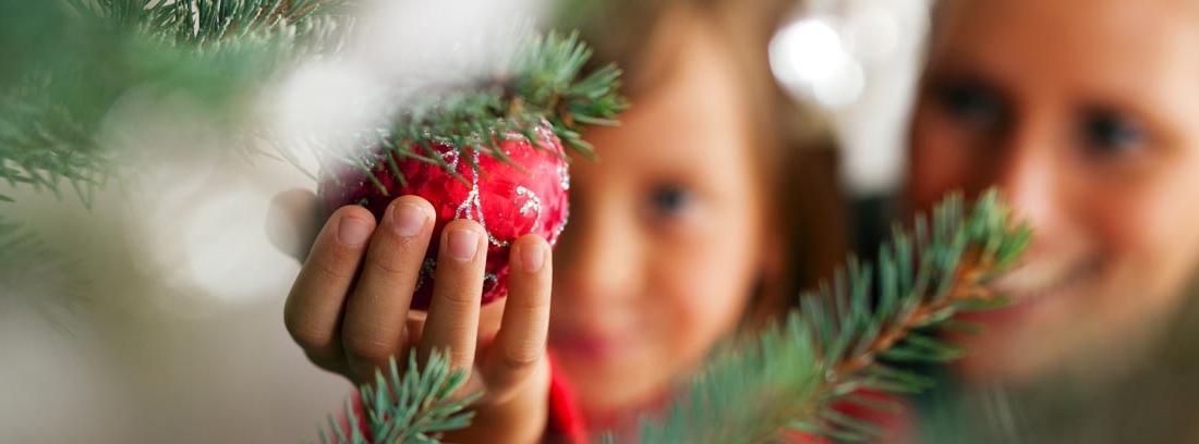 Niño colocando adornos de navidad caseros en un árbol hecho con palos de madera, junto a un hombre con un niño pequeño en brazos