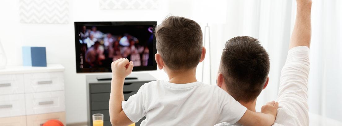 Hombre y niños de espaldas sentados en un sofá con los brazos arriba y frente a un televisor