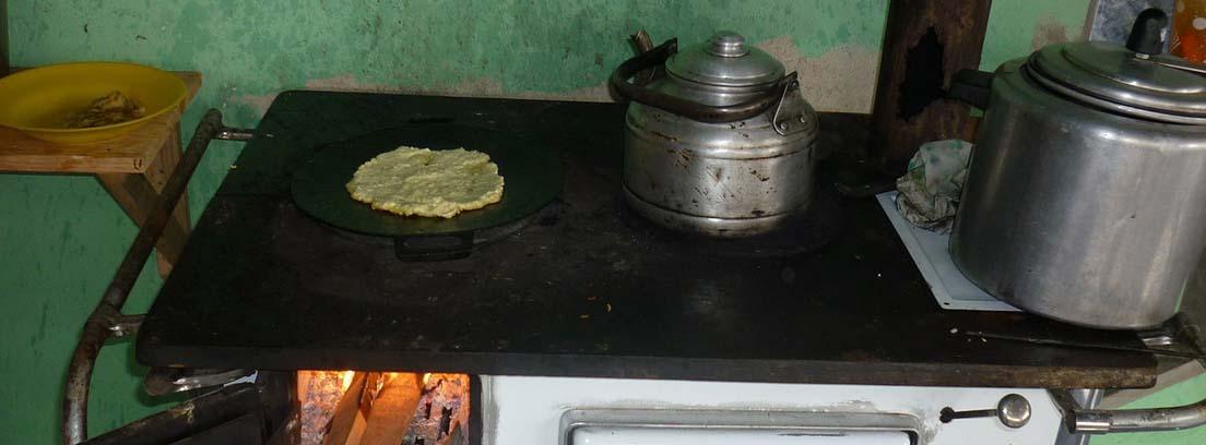 Cocina de leña con zona de leña abierta y cacharros sobre ella