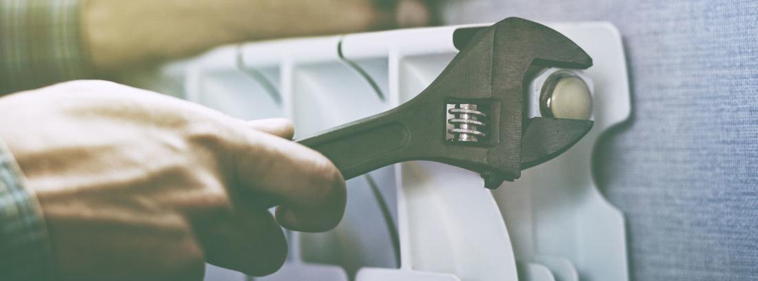 Manos sostienen una llave inglesa para arreglar un radiador