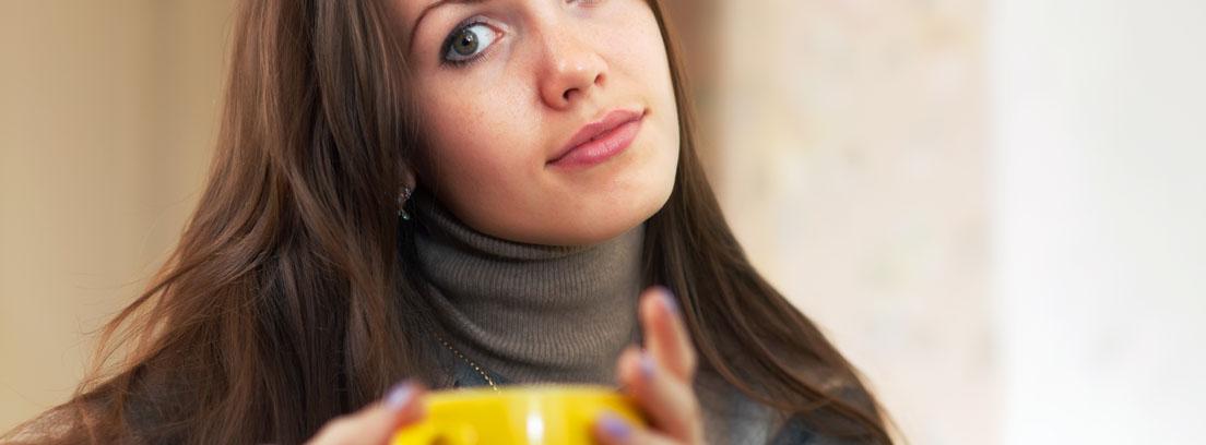 Mujer apoyada en un radiador con una manta y una taza en la mano
